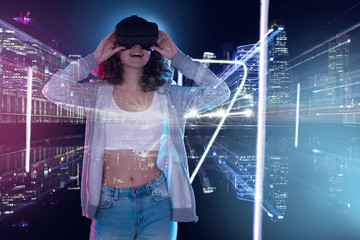 Teenage curly girl is playing in game club. Smiling surprised young woman in VR glasses is watching 3d virtual city tour in simulator. Entertainment and leisure concept. Modern technologies. Wall mural
