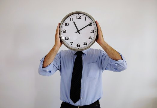 Man Covering Face With Clock Against Wall