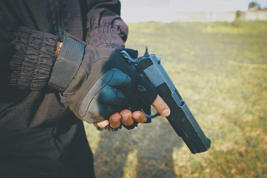 Midsection Of Burglar Holding Handgun On Lawn