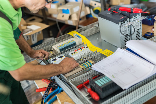 Electrician assembling industrial electric cabinet in workshop.