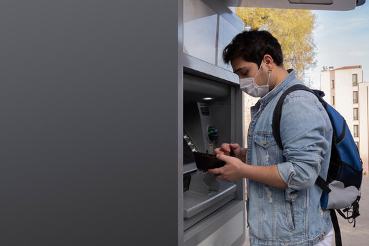 The young man performs his transactions from the bank atm using his protective mask.