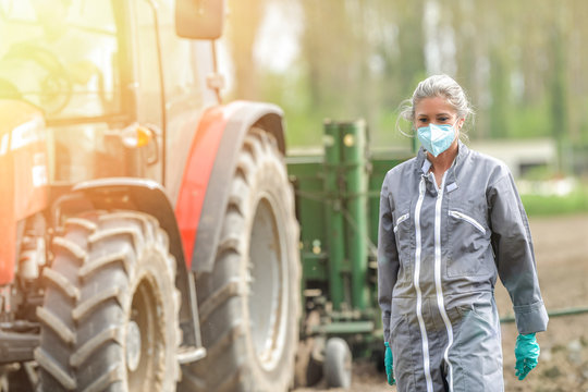Portrait of a woman  farmer wearing her protective mask in the field beside a tractor