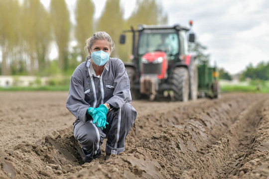 Female farmer  analyses the soil before planting and wearing a protective mask against coronavirus