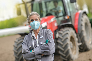 Female farmer standing in front of a tractor and wearing a protective mask against covid-19