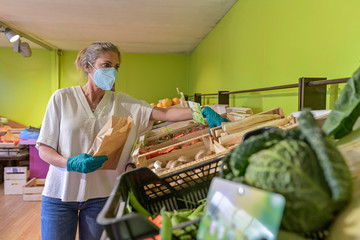 Woman buying fruits and vegetables direct from producer during confinement and wearing her protective mask in the shop