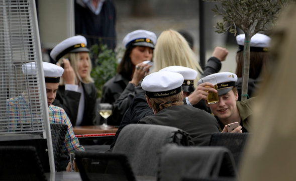 Swedish high school final year students wearing their characteristic caps celebrate their graduation at an outdoor restaurant in central Stockholm
