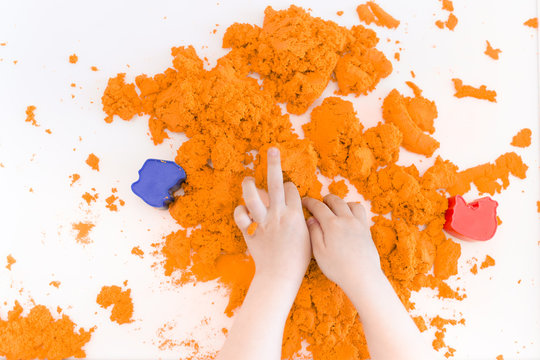 Orange magic sand in a kids hands on a white background close up. Early sensory education. Preparing for School. Development