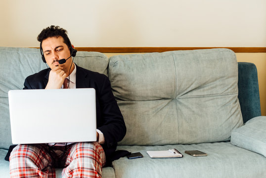 Executive businessman with a mask on his face working from home with his laptop Dressed in a suit and tie and pajama pants. Laptop and headphones. Concept work from home. Coronavirus pandemic.