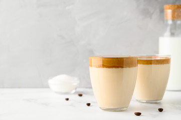 Korean coffee drink. Iced Dalgona coffee in two glass cups on light table. Trendy refreshment creamy whipped coffee. Horizontal orientation, copy space. Gray concrete background