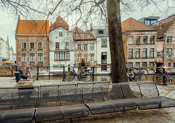 City bicycles parked past river of historical town with old brick walls bildings
