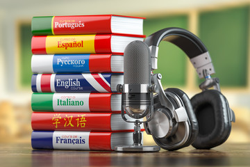 Learning languages online.  Dictionary books of different languages with headphones and microphone. Fotobehang