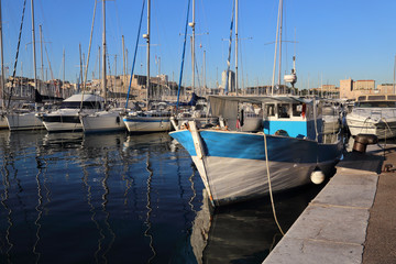 Traditional fishing boat and sailboats in the old port of Marseille, France