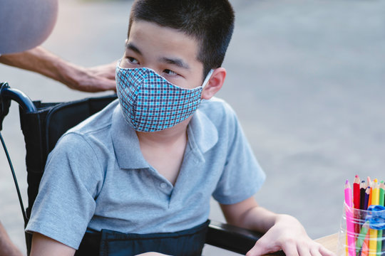 Asian Special need child on wheelchair wearing a cotton mask by parent, The boy doing home work, Study and Working at home for safety from covid 19, Life in education age of disabled children.