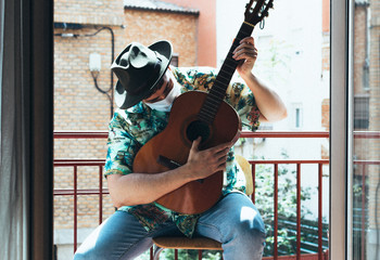 Bohemian musician with mask on his face and hat playing the Spanish guitar from his balcony....