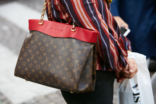 Woman with Louis Vuitton bag with red border and striped shirt on September 23, 2017 in Milan, Italy
