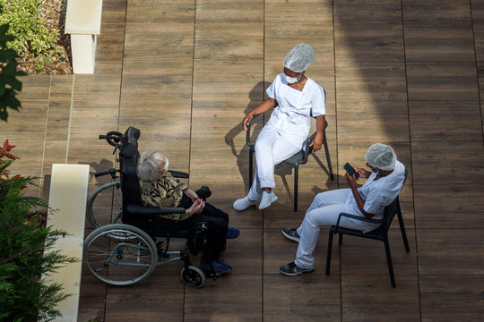 Nurses caring for elderly or disabled people in a nursing home during the coronavirus pandemic Covid-19. Carers having a break in th sun with an old woman resident.