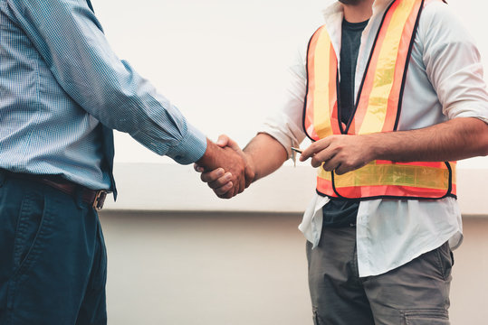 Midsection Of Businessman Shaking Hands With Architect At Construction Site