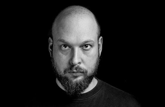 Portrait Of Shaved Head Man Against Black Background