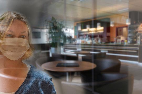 frau mit mundschutz schaut durch eine glasscheibe  in ein geschlossenes cafe