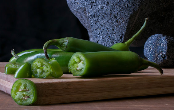 Molcajete and serrano peppers or chiles serranos on a wooden cutting board chiaroscuro, low key light still life