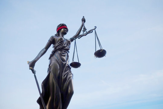Justitia Lady justice statue with blindfold against blue sky