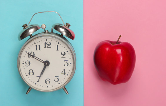 Apple, alarm clock on pink blue background. Back to school. Education concept. Top view