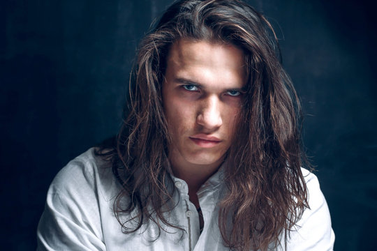 Handsome calm man. Portrait of a young muscular guy with long hair. Strong boy on an isolated dark background in the studio