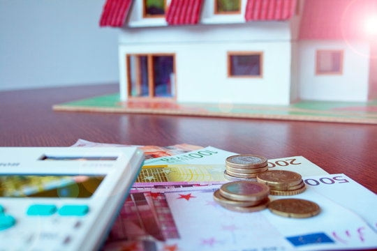 home insurance concept with blurred background focused on bills, coins and calculator, house concept on background.