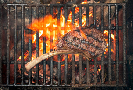 tomahawk steak cooking on flaming grill