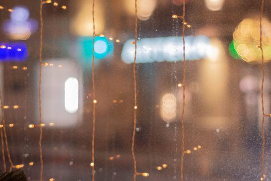 Full Frame Shot Of Wet Glass Window With String Lights