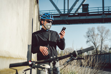 The courier in protective mask on bicycle stopped and was watching the phone application. Delivery service in quarantine. A man in a respirator uses a mobile phone. Bicycle messenger works