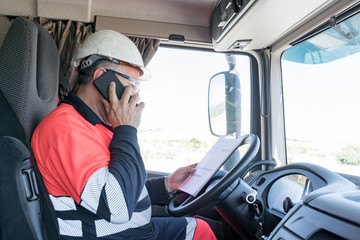 Truck driver with helmet, safety glasses and high visibility clothing talking on the phone and with a folder reviewing notes