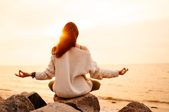 Inspirational photo of a girl who sitting in lotus position and meditates at sunset by the sea