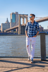 Fototapete - Young guy standing by the Hudson river in New York city.