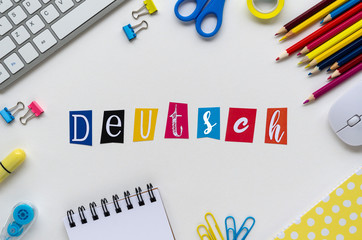 Word DEUTSCH made with colorful letters on a white table with keyboard and school stationery. Top...