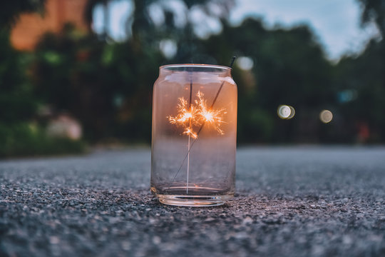 Close-up Of Sparklers Burning In Jar On Road
