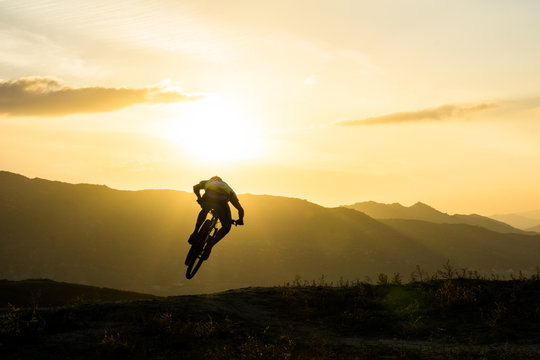 Rear View Of Man With Bicycle Performing Stunt On Mountain Against Sky During Sunset