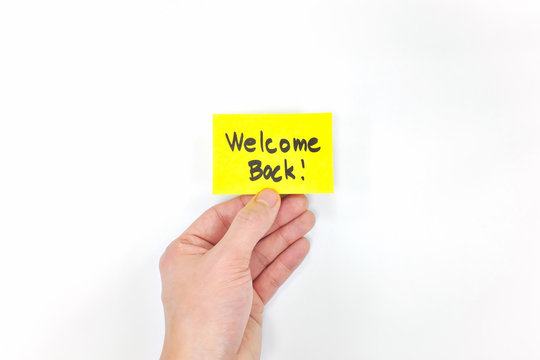 Hand holding yellow welcome back note in white background. Back to work, school and office concept.