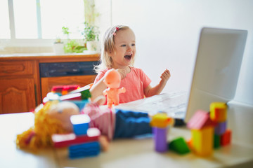 Happy toddler girl with laptop and toys
