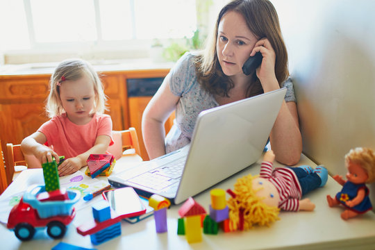 Exhausted and stressed mother working from home with toddler