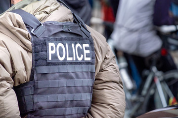 A close up of a male undercover police officer stands on a street among a crowd of people. The officer has a black canvas bulletproof vest on with the word police spelled out in white letters.