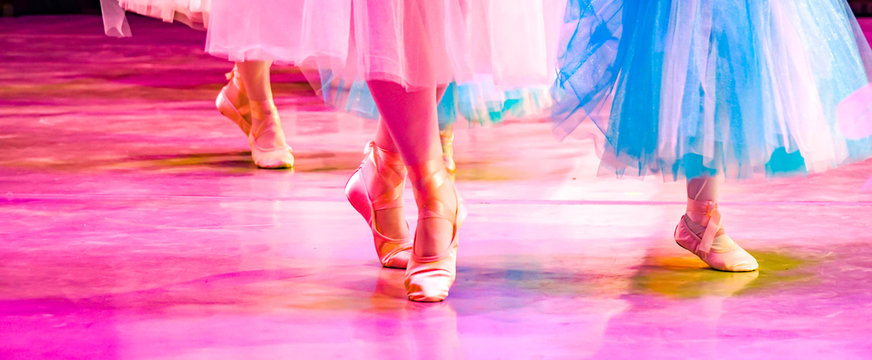 colorful ballet, female legs in pointe shoes on stage, large, blue and pink ballet tutus