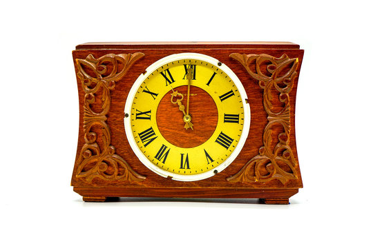 old brown carved antique wooden watch with yellow dial, Roman numerals and metal arrows, isolate on a white background, 11 o'clock