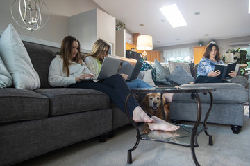 Mother and two daughters reading and working on computer together at home in living room