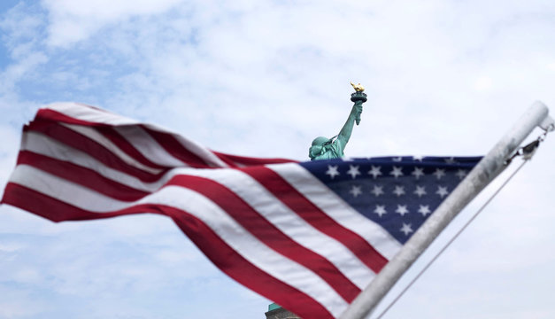 Low Angle View Of American Flag With Statue Of Liberty In Background