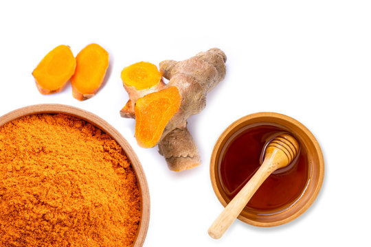 Dry turmeric power in wooden bowl and fresh curcuma root with pure gold honey isolated on white background. Top view. Flat lay.