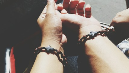 Cropped Hands Of Couple Wearing Rosary Bracelets