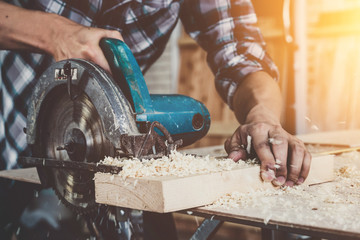 Fototapeta Carpenter working on wood craft at workshop to produce construction material or wooden furniture. The young Asian carpenter use professional tools for crafting. DIY maker and carpentry work concept. obraz