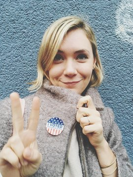 Smiling Beautiful Woman Wearing Campaign Button Gesturing Peace Sign