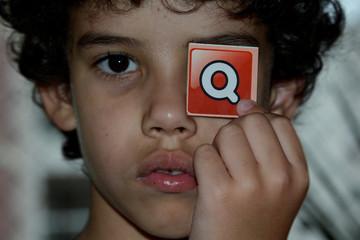 Portrait Of Boy Holding Q Sign